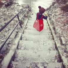 Photo of a preschool boy taking one Butterfly Box down snowy steps on the way to the airport.